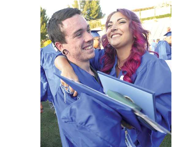 Matt D Amico and Amber Demento hug after receiving their diplomas at the end of the Bowman High School graduation held at College of the Canyons in Valencia on Saturday.