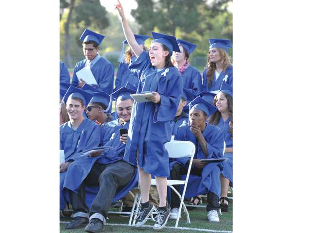 Cassidy Luyando cheers for a friend during the awarding of diplomas ceremony at the Bowman High School graduation held at College of the Canyons in Valencia on Saturday.