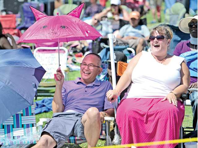 Rudy Margono, left, and Windie Murphy of Valencia enjoy the entertainment on stage at the inaugural GraceFest SCV fundraiser event held at Central park on Saturday.