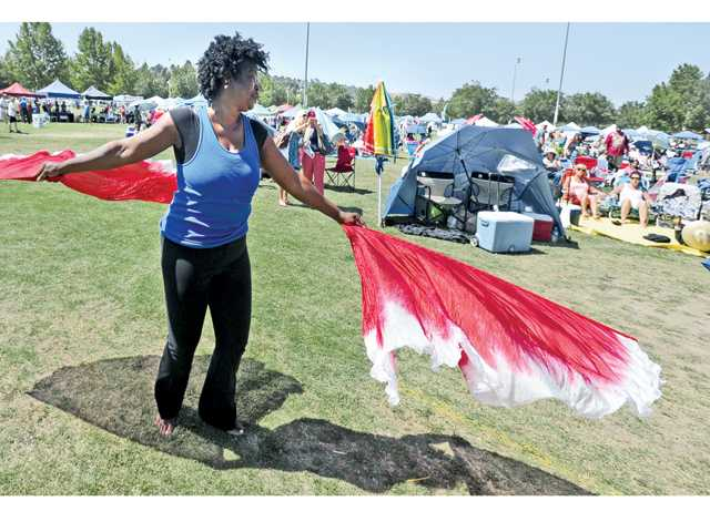 Carrie Duren dances with brightly colored flags as hundreds of attendees listen to the music performed on stage at the inaugural GraceFest SCV fundraiser event held at Central Park on Saturday.
