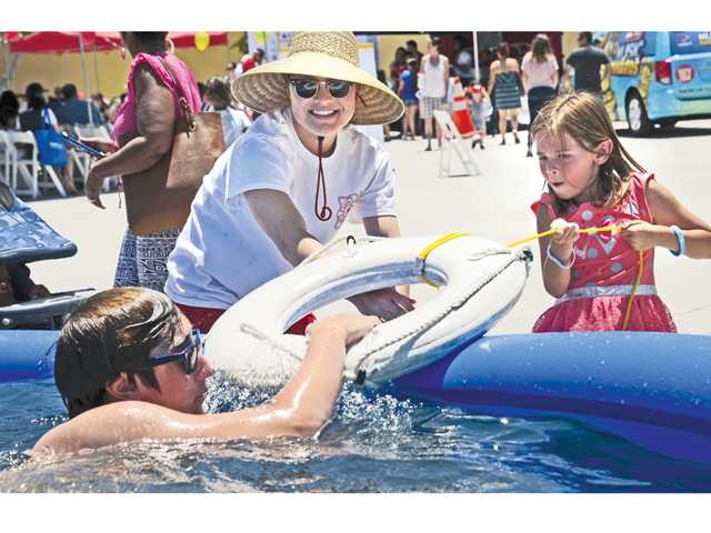 Skyler Presley, 6, right, of Saugus gets instruction in pool-side life-saving from city of Santa Clarita lifeguards Keone Thompson, left, and Kristen Kabach at the Water Safety Expo.
