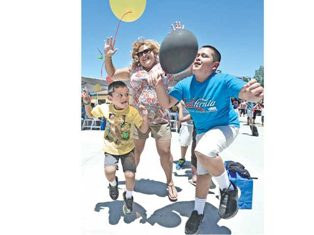 Griselda Cervantes, center, and her sons Sammy, 5, left, and Silvester, 11, compete in a Radio Disney dance competition at the Water Safety Expo held at Fire Station 126 in Valencia on Saturday.