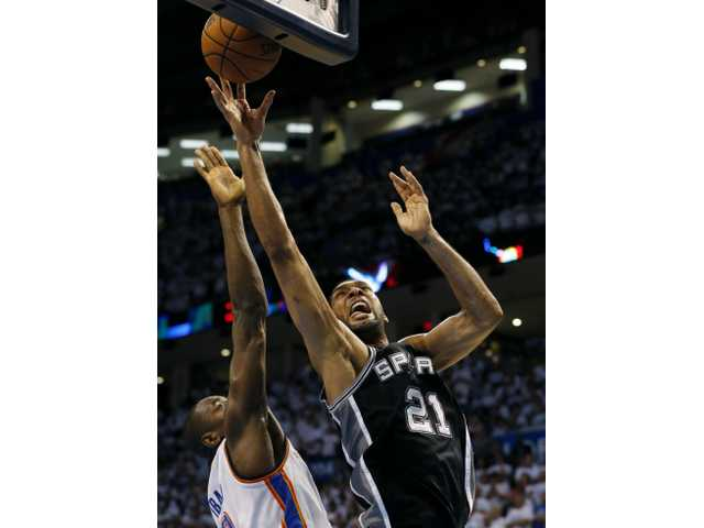 San Antonio Spurs forward Tim Duncan shoots against Thunder forward Serge Ibaka in overtime of Saturday's Game 6 in San Antonio.