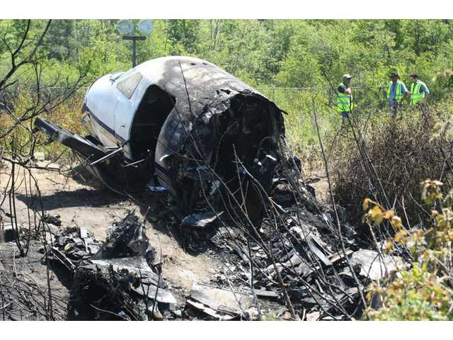 Officials work near wreckage at the scene Monday in Bedford, Mass., where a plane plunged down an embankment and erupted in flames during a takeoff attempt at Hanscom Field on Saturday night.