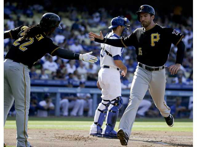 Pittsburgh Pirate Ike Davis, right, celebrates with teammate Andrew McCutchen while Los Angeles Dodgers catcher Drew Butera looks on Sunday in Los Angeles.