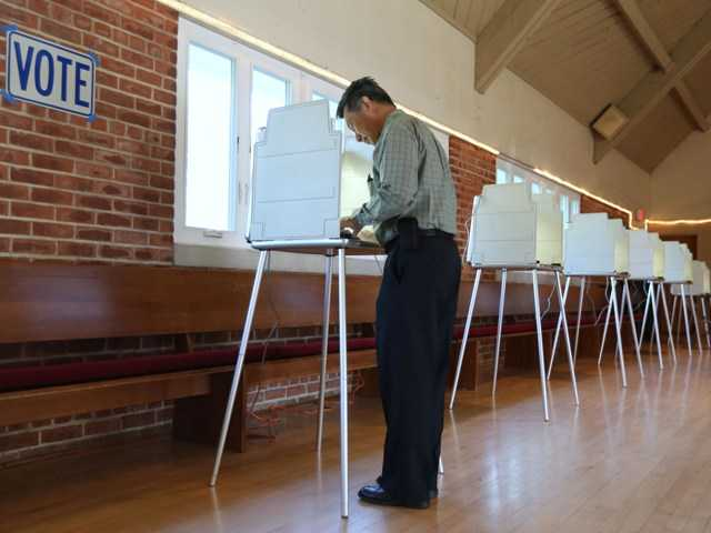 Mike Lee marks his ballot while voting in the California Primary, in Sacramento,Calif.
