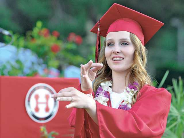 Hart High School graduating senior Courtney Nix uses sign language to interpret the National Anthem at COC's Cougar Stadium in Valencia during their graduation ceremony on Tuesday. Signal photo by Dan Watson.