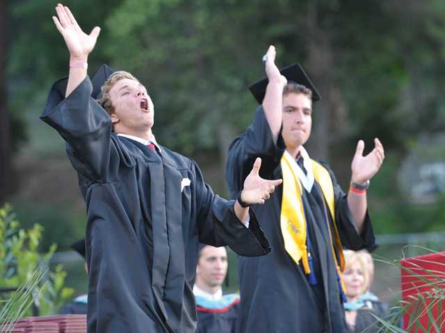 Hart High School graduating seniors Pearson Good, left, and Erik Stafford lead a Hart High cheer in front of the graduating class during the ceremony. Signal photo by Dan Watson.