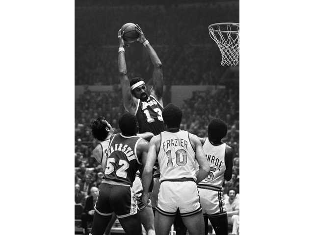 In this May 8, 1973 file photo, Los Angeles Lakers center Wilt Chamberlain towers over teammate Happy Hairston and New York Knicks players, from left, Dave DeBusschere, Walt Frazier and Earl Monroe, during an NBA playoff game at Madison Square Garden in New York. It's been 33 years since teams from these cities played for a title. The rivalry could be lost on many fans when the Kings and Rangers meet for the Stanley Cup.