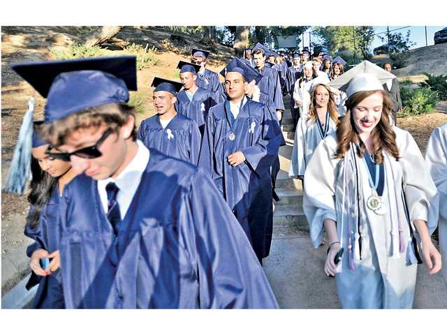 Saugus High School graduates walk down the steps into Cougar Stadium at College of the Canyons on Wednesday. Signal photo by Katharine Lotze.
