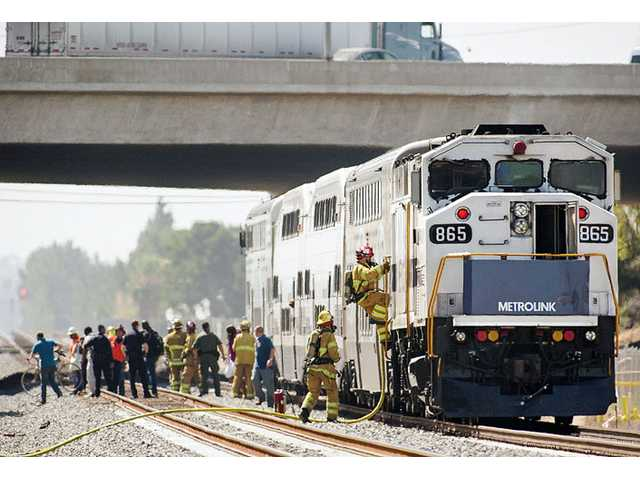 Firefighters enter a Metrolink commuter train as commuters are moved Thursday, June 5