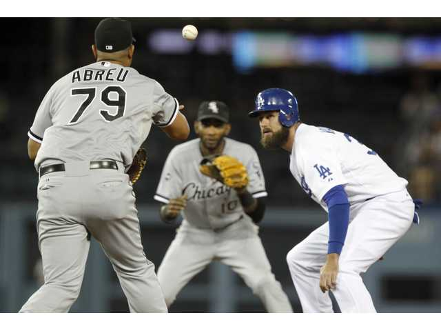 Los Angeles' Scott Van Slyke gets caught in a rundown between the Chicago's Jose Abreu and Alexei Ramirez in Wednesday's game in Los Angeles..