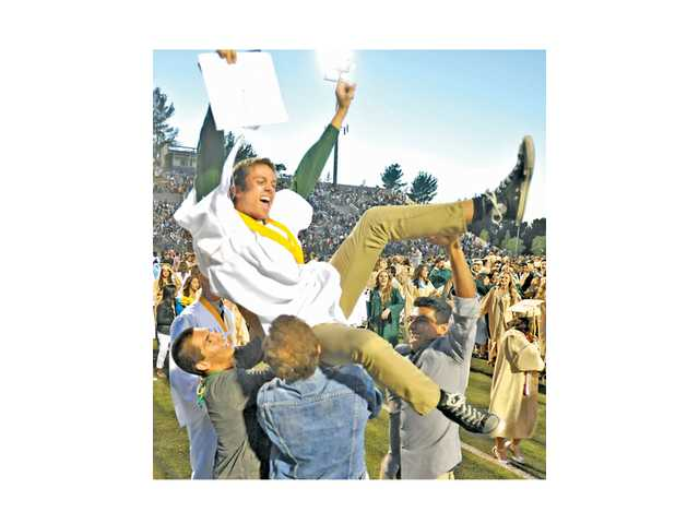 Newly-minted Canyon graduate Adam Driedger gets hoisted in the air by friends following the high school's commencement ceremony. Signal photo by Katharine Lotze.