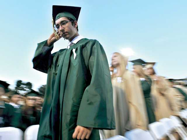 Matthew Johnson walks to the stage to get his diploma at Canyon High School's graduation ceremonies at College of the Canyons on Thursday.Signal photo by Katharine Lotze.