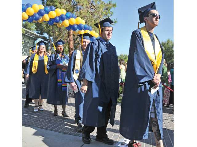 Some of the 1,343 graduating students march in during the 2014 commencement ceremony at College of the Canyons on Friday. Signal photo by Dan Watson