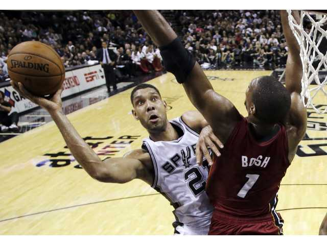 Spurs forward Tim Duncan, left, shoots over Miami's Chris Bosh during Thursday's Game 1 in San Antonio.
