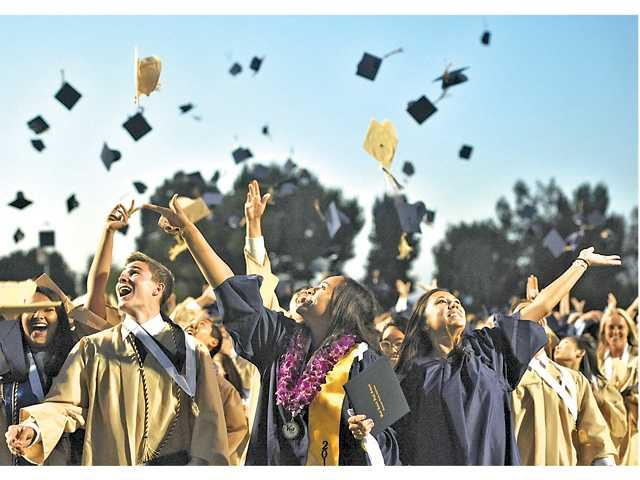 West Ranch High School graduates toss their caps at College of the Canyons on Friday.