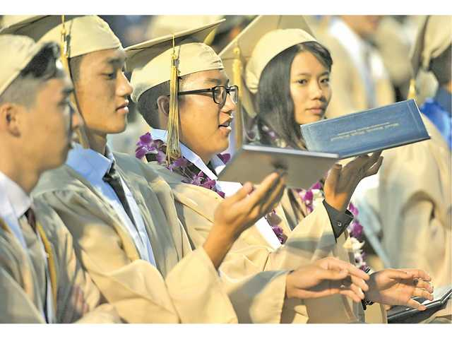 West Ranch graduates Jonathan Lee and Jonathan Lee spin their diploma covers at their commencement ceremony at College of the Canyons on Friday.