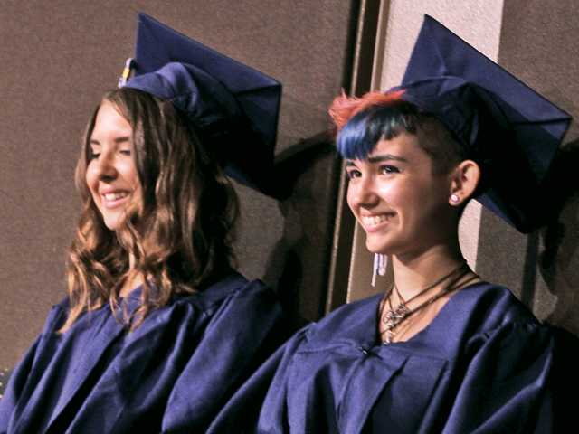 Kerry Murphy, left, and Ashlyn Sanchez, right, await their turn to speak to their fellow graduates of Santa Clarita Valley International Charter School in the Shakespeare Theater on Friday night.