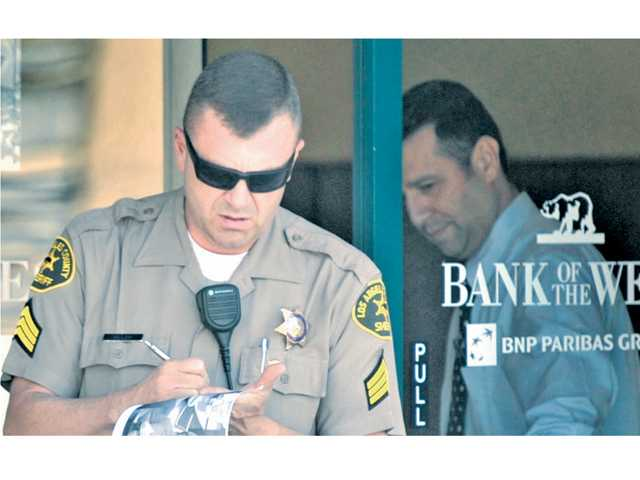 A sheriff's deputy gathers evidence at the scene of a attempted robbery at Bank of the West on Magic Mountain Parkway on Friday.
