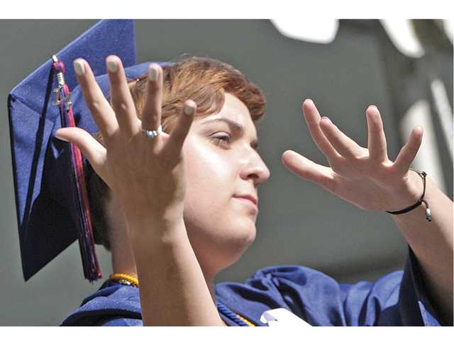 Graduating senior Tambrie Rose uses sign language to interpret the National Anthem for the crowd during the 2014 Academy of the Canyons commencement ceremony held at College of the Canyons in Valencia on Saturday morning.