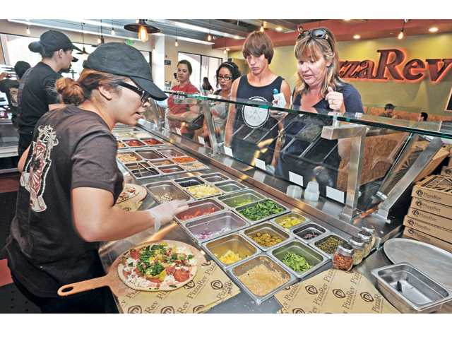 PizzaRev crew member Stephanie Lopez, left, creates a pizza to order from the dozens of toppings available to Louis and Michele Eusebi. Dan Watson/The Signal