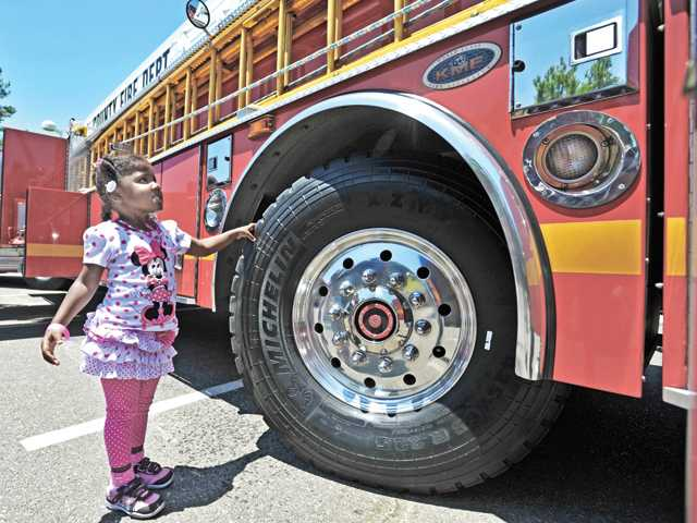 In this Signal file photo, Adrienne Meeks, 3, checks out Los Angeles County Fire Quint 126 during last year's Touch-A-Truck event at Central Park in Saugus.