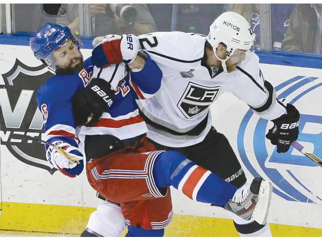 New York Rangers right wing Martin St. Louis, left, collides with Los Angeles Kings center Trevor Lewis during Game 3 of the Stanley Cup Final on Monday in New York.