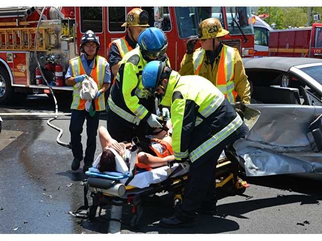 L.A. County firefighter/paramedics and AMR ambulance personnel treat a female patient injured in a traffic collision in Stevenson Ranch on Monday. Rick McClure/For The Signal