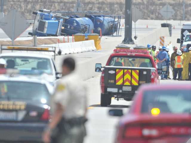 First responders and workers from the California Department of Transportation keep their distance from a tanker truck that overturned, spilling a chemical on the roadway on Highway 126 near Commerce Center Drive in Castaic on Tuesday morning. Signal photo by Dan Watson.