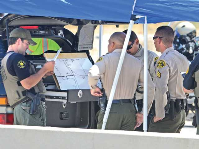 Deputies discuss a map of roadways adjacent to a closed portion of Highway 126 near Commerce Center Drive where a tanker truck overturned, spilling a chemical on the roadway in Castaic on Tuesday morning. Signal photo by Dan Watson.