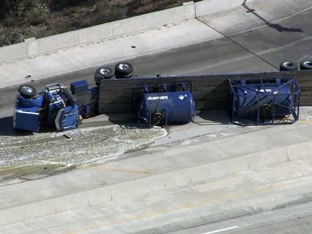 An aerial view of the overturned tanker truck shows its load leaking from a damaged area at the top of the tanker. Officials identified the truck's load as fuel. Photo courtesy of KTLA Channel 5 News.