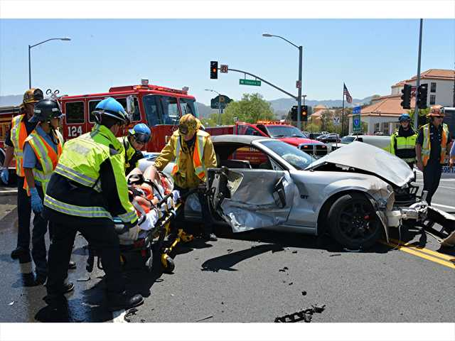 Firefighter paramedics place another woman on a stretcher after freeing her from a wrecked car following a three-vehicle accident in Stevenson Ranch Monday. Photo courtesy of Rick McClure.