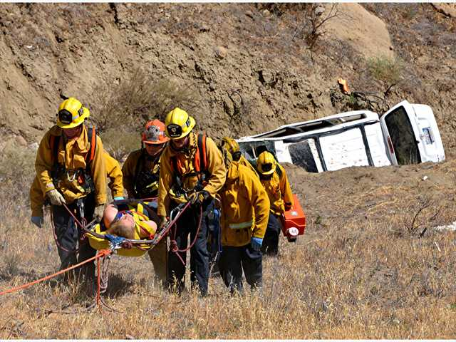 Firefighters carry an injured woman up a ravine after her van veered off Vasquez Canyon Road Monday. Photo courtesy of Rick McClure.
