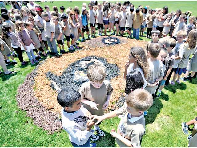"Students at Mountainview Elementary wait for fellow students to fill in the bear shape for Daniel Dancer's ""Art for the Sky"" project at Pacific Crest Park in Saugus on Tuesday. Signal photo by Katharine Lotze."