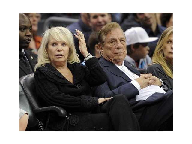 In this Nov. 12, 2010, file photo, Shelly Sterling sits with her husband, Donald Sterling, right, during the Los Angeles Clippers' NBA basketball game against the Detroit Pistons in Los Angeles. An individual with knowledge of negotiations to sell the Clippers says Shelly Sterling has reached an agreement to sell the team to former Microsoft CEO Steve Ballmer for $2 billion. The individual, who wasn't authorized to speak publicly, told The Associated Press on Thursday, May 29, 2014, that Ballmer and the Sterling Family Trust now have a binding agreement. The deal now must be presented to the NBA. (AP Photo/Mark J. Terrill, File)