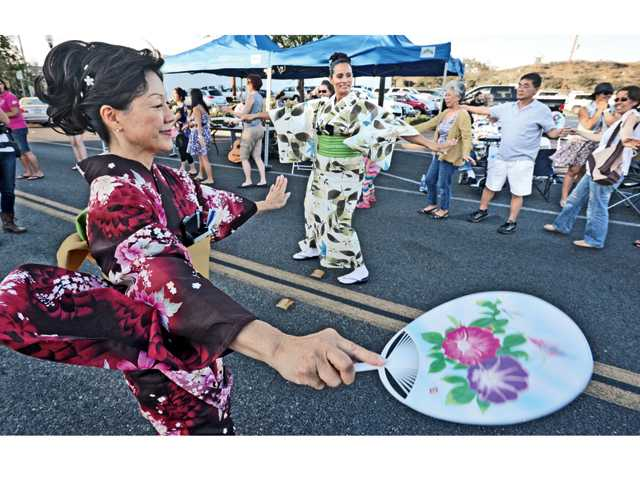 Japanese dancers Debbie Nicklaus, left, and Monica Cruz of Japanese folk fusion ensemble Minyo Station demonstrate Japanese folk dance and music as attendees follow along at the Jam Sessions event held on Main Street in Newhall on Thursday. Signal photo by Dan Watson.