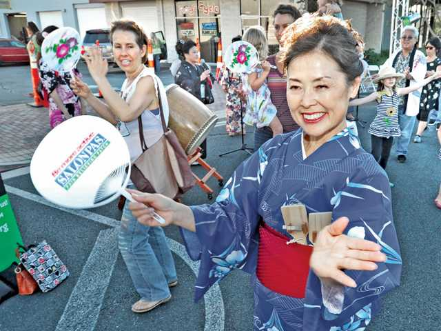 Japanese dancer Satomi Nishimoto of Japanese folk fusion ensemble Minyo Station demonstrates Japanese folk dance and music as attendees follow along at the Jam Sessions event held on Main Street in Newhall on Thursday. Signal photo by Dan Watson.