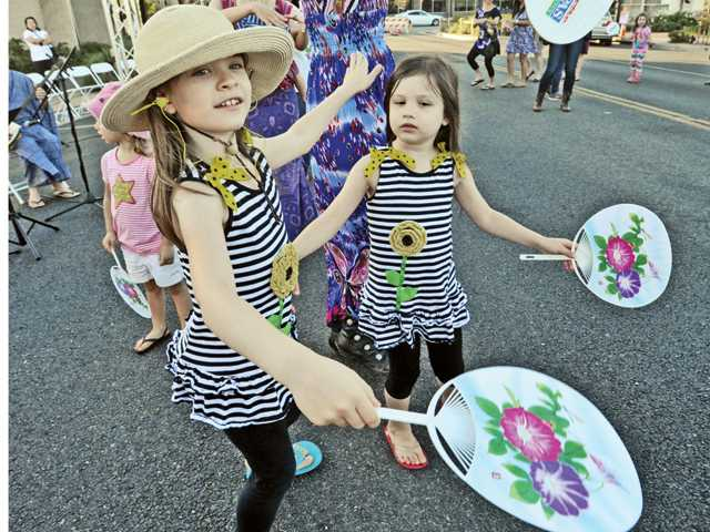 Lily, left, and Hannah Fitelson of Valencia follow along during a Japanese folk dance and music denomination at the Jam Session event held on Main Street in Newhall Thursday evening. Signal photo by Dan Watson.