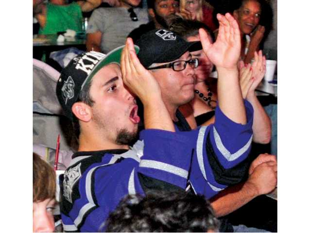 Blake Rossi celebrates a close save by the Kings while watching the game at Ice Station Valencia.
