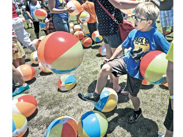 Cole Keller, 8, kicks a one of the 224 beach balls that were dumped from the bed of a City of Santa Clarita dump truck at the second annual Touch-A-Truck, a family friendly event held at Central Park in Saugus on Saturday. Signal photo by Dan Watson.