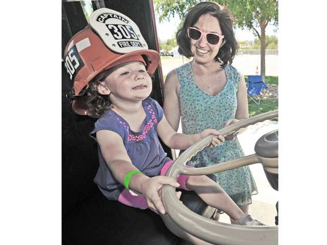 Aunt Hannah Endicott looks on as three-year-old Harper Fleck gets her hands on the wheel of a fire truck at the second annual Touch-A-Truck, a family friendly event held at Central Park in Saugus on Saturday. Signal photo by Dan Watson.