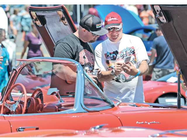 Car enthusiasts Josh Christensen, left, and Ron Nolan take photos as they examine some of the 13 Corvettes on display from the Santa Clarita Valley Corvette Club at the High Octane Charity Car Show to benefit The Gentle Barn held at the Saugus Speedway in Saugus on Saturday. Signal photo by Dan Watson.