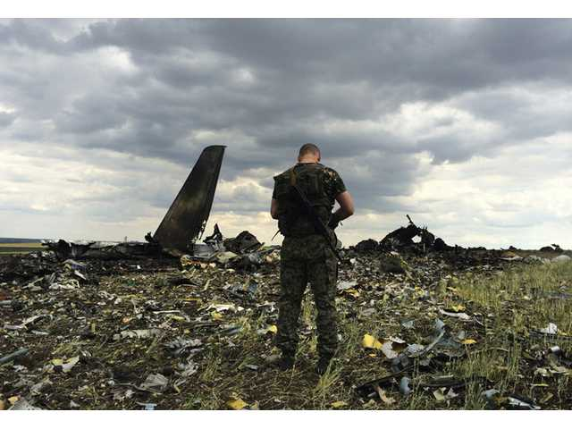 A pro-Russian fighter guards the site of remnants of a downed Ukrainian army aircraft Il-76 on Saturday, June 14.