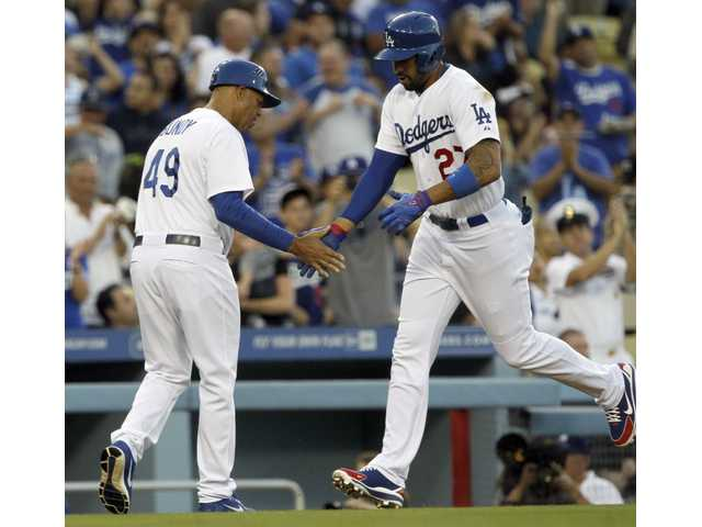 Los Angeles Dodgers third base coach Lorenzo Bundy, left, congratulates Matt Kemp, right, after Kemp hit a two-run home run against the Arizona Diamondbacks on Friday in Los Angeles.