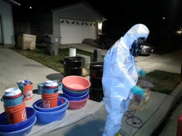 In this March 2014 photo provided by PARC Environmental, Jeff Davis, a hazardous materials specialist for PARC Environmental, cleans up a meth conversion lab inside a house in Madera, Calif.