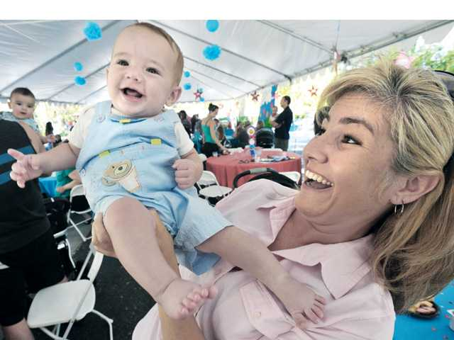 NICU graduate Milos Healey, 9 months, is held up by his mother Jara of Saugus.