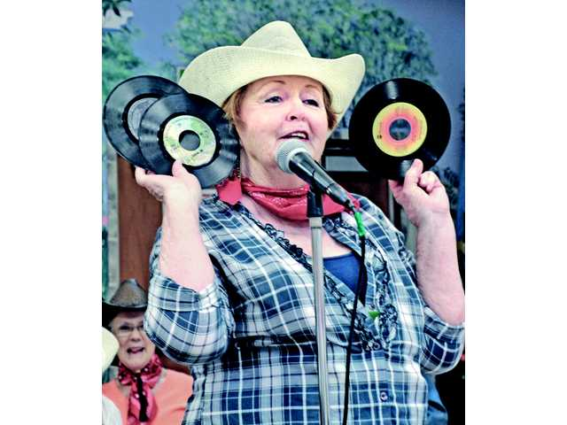 "Betty Parente pulls old records from her shirt as she sings ""She's Got You."""