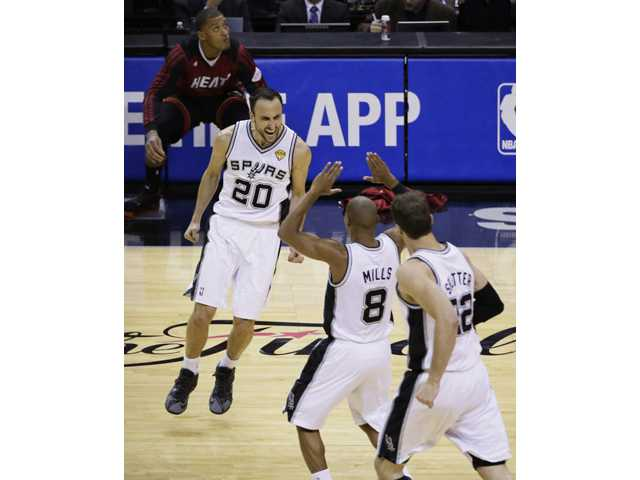 San Antonio Spurs guard Manu Ginobili (20), guard Patty Mills (8) and center Tiago Splitter (22) celebrate against the Miami Heat on Sunday in San Antonio.