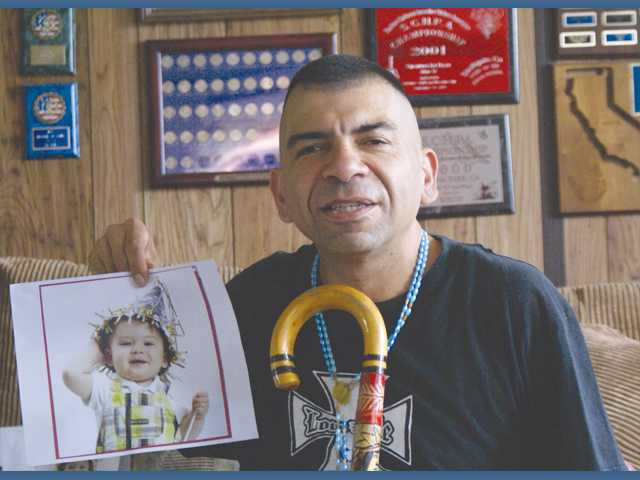 Tony Martinez holds a picture of his grandson Aires, one of four grandchildren, in his Santa Clarita home.